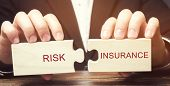 Businessman Collects Wooden Puzzles With The Word Risk Insurance. The Transfer Of Certain Risks To T poster
