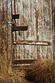 picture of hasp  - A rural garage in disrepair shows a locked door and tumbleweed blown against it - JPG