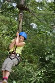 stock photo of parkour  - Preteen girl is zipping down at the rope parkour outdoors - JPG