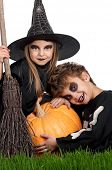 stock photo of warlock  - Boy and girl wearing halloween costume with pumpkin on white background - JPG
