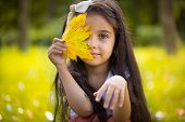 foto of gypsy  - Cute hispanic little girl hiding over yellow leaf - JPG