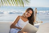 Pretty brunette sitting on hammock with laptop smiling at camera on the beach