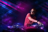 stock photo of mixer  - Attractive young DJ playing on turntables with color light effects - JPG