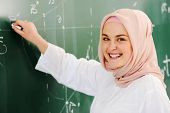 foto of muslim man  - Arabic Muslim teenage student inside the high school classroom posing on board - JPG