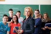 stock photo of teacher  - Group of students with a teacher in a classroom - JPG