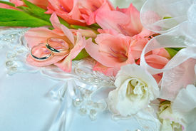 stock photo of gladiola  - Gladiola bridal bouquet with wedding rings on satin pillow.