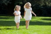 foto of young girls  - Two pretty young blond girls wearing white dresses and having fun running through a green park in summer sunshine - JPG