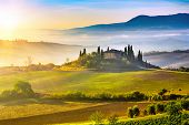 stock photo of farmhouse  - Tuscany foggy landscape at sunrise - JPG