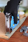 Fastening fabric and board using construction stapler on bright background