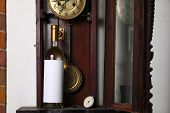 picture of pendulum clock  - Bottle of white wine with blank label template standing inside an old clock - JPG