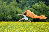 picture of leaping  - Agile barefoot woman with curly brown hair leaping in the air in a meadow of yellow wildflowers trailing a colorful orange scarf in the breeze as she celebrates her freedom and the beauty of nature - JPG