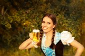 image of stein  - Young woman in German dress holding a glass beer mug - JPG
