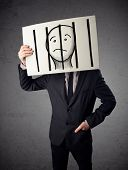 stock photo of jail  - Businessman holding a paper with a prisoner in jail behind the bars on it in front of his head - JPG
