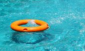 Постер, плакат: Orange Life Buoy Floating On The Surface Of Blue Water