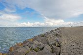 foto of dike  - Clouds over a dike in a lake - JPG