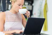 stock photo of independent woman  - Business woman working remotly from her dining table while having her morning coffee - JPG