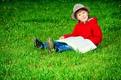 stock photo of 7-year-old  - Cute 7 years old boy sitting on a grass with a book - JPG