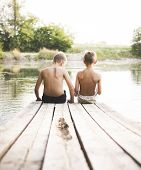 pic of dock a pond  - Boys sitting on a pier in the water in summer in their swimming trousers - JPG