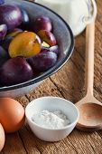 pic of baking soda  - Ingredients to bake a plum cake on a rustic wooden table - JPG