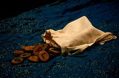 stock photo of rune  - A plain muslin bag with wooden runes spilling out over a sparkling blue cloth.
