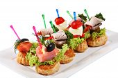 image of canapes  - Many small canape sandwiches on colored plastic skewers put on a plate isolated on a white background.