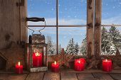 pic of mood  - Country christmas decoration: wooden window decorated with red candles and latern.