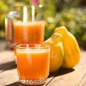 stock photo of papaya  - Glass of freshly prepared papaya juice with pitcher and papaya fruits in the back on table outdoors  - JPG