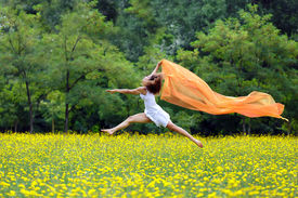 foto of barefoot  - Agile barefoot woman with curly brown hair leaping in the air in a meadow of yellow wildflowers trailing a colorful orange scarf in the breeze as she celebrates her freedom and the beauty of nature - JPG