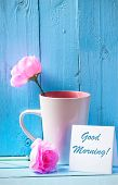 stock photo of blue rose  - Mug with pink roses on blue wood background with good morning text