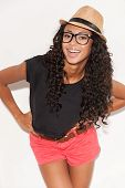picture of young woman posing the camera  - Beautiful young African woman in glasses and funky wear holding hands on hip and smiling at camera while posing against white background - JPG