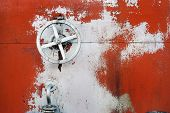image of big-rig  - old big hand wheel on the wall of oil tank - JPG