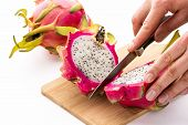 picture of cross-section  - Closeup of a dragonfruit being halved with a longitudinal cut through its core - JPG