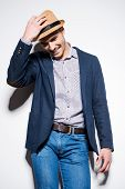 stock photo of fedora  - Handsome young man in smart casual wear adjusting his fedora and smiling while standing against a wall - JPG