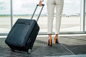 foto of carry-on luggage  - Rear view of businesswoman in formalwear carrying suitcase while walking away with airplanes in the background - JPG
