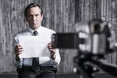 stock photo of revenge  - Frustrated businessman caught by a criminal sitting in front of a dirty wall and holding paper while video camera filming it on the foreground - JPG