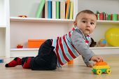 image of cute innocent  - Portrait of a cute baby playing with car toy in children - JPG