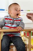 foto of child feeding  - Hungry little baby child eating porridge food - JPG