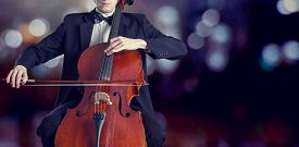stock photo of classic art  - Cellist playing classical music on cello on bokeh background - JPG