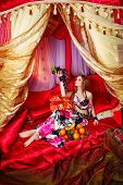image of harem  - Oriental beauty sit on cushions in her tent and holding a grape - JPG