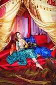stock photo of harem  - Oriental beauty sitting in a tent and holding a fruit platter - JPG