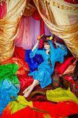 foto of harem  - Young oriental beauty sitting in a tent and holding on her head a dish with fruits - JPG