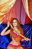 stock photo of harem  - Sexy oriental beauty sitting in a tent and holding a sword with both hands - JPG