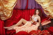 stock photo of harem  - Sexy oriental beauty is in the tent on the pillow and holding jewelry - JPG