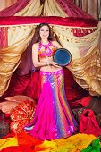 stock photo of harem  - Sexy oriental beauty dancing and playing the tabla pleasant melody - JPG
