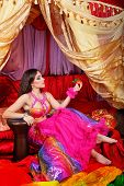foto of harem  - Sexy oriental beauty rests his hand on tabla and holds a tangerine - JPG