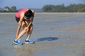 picture of ankle shoes  - young woman runner holds her twisted ankle - JPG
