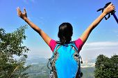 stock photo of open arms  - young cheering woman hiker open arms at mountain peak - JPG
