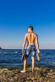 image of nearly nude  - Attractive handsome sexy naked young man on rock near the sea water with shoes in hand - JPG