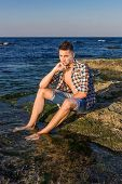 pic of nearly nude  - Attractive young fashion sexy man sitting on a rock near the sea water - JPG