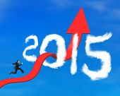 pic of bend  - Businessman running on red arrow upward bending trend line breaking through 2015 shape clouds and blue sky background - JPG